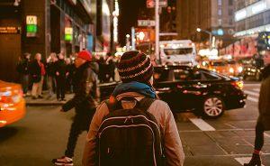 Chica con mochila cruzando calle ciudad a la noche.