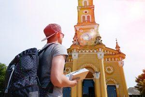 Chico lee una guía de viaje frente a una iglesia amarilla.