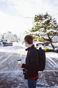 Chico con un vaso térmico y mochila en el frío.