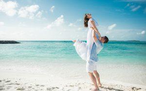 Novios enamorados en una playa con mar turquesa
