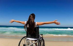 Turismo accesible Mujer silla de ruedas arena playa mar