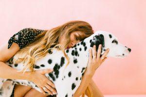 Mujer abraza a su perro dálmata en habitación rosa