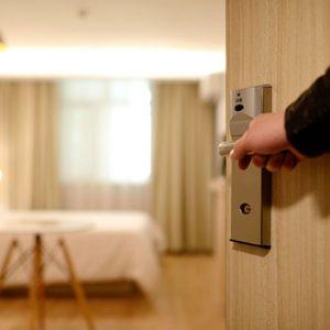 Abre puerta de habitación de hotel.