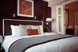 Habitación y cama de hotel con decoración bordo