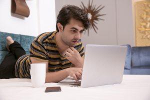 Hombre mirando streaming en la laptop en la cama