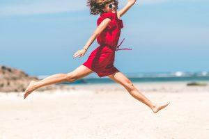 Mujer feliz saltando con vestido rojo en una playa