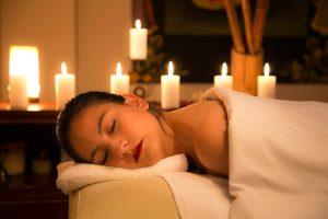 Mujer en una sesión de spa, masaje, relajación y velas