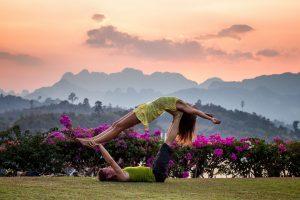 Pareja practicando Yoga al aire libre en un paisaje